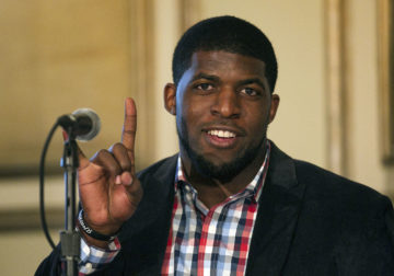 Former Texas Longhorn Emmanuel Acho, a linebacker with the Philadelphia Eagles, gives a Hook'Em before taking part the session, Paid to Play: The Future of College Athletics during South by Southwest 2014.